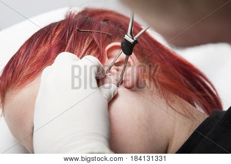 Piercing professional gripping the skin ear before inserting the cannula. Tragus type