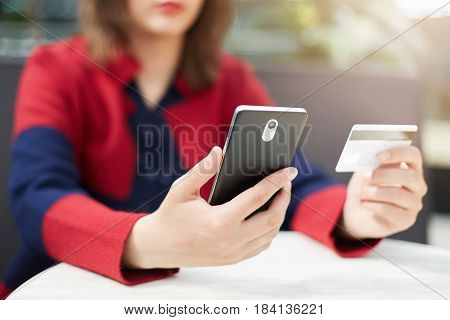 A Woman In Red Clothes Holding Mobile Phone In Hands Paying With Credit Card Online While Making Ord