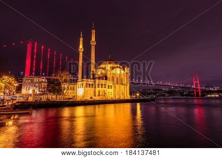 Ortakoy Camii mosque with two  minarets backlighted shot at blue hour with new bridge as background, Istanbul, Turkey.