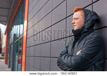 A Sideways Portrait Of Fashionable Guy With Trendy Red Hair Wearing Black Jacket And Hood On His Hea