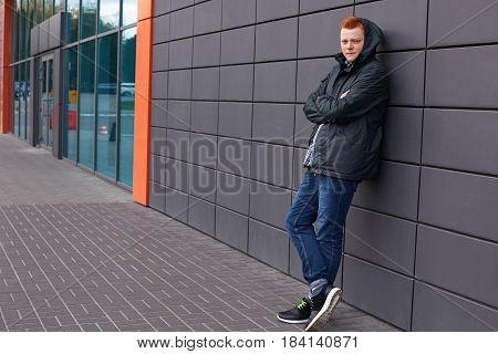 A Horizontal Portrait Of Young Fashionable Guy With Trendy Red Hair Dressed In Black Jacket, Jeans A