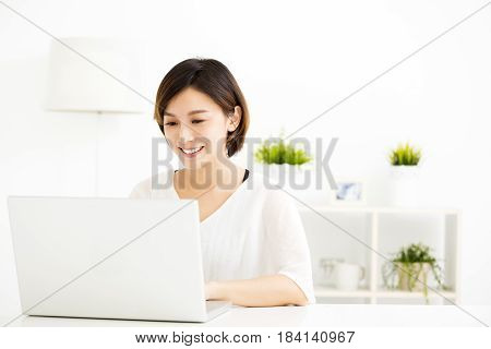 happy young woman with laptop in living room