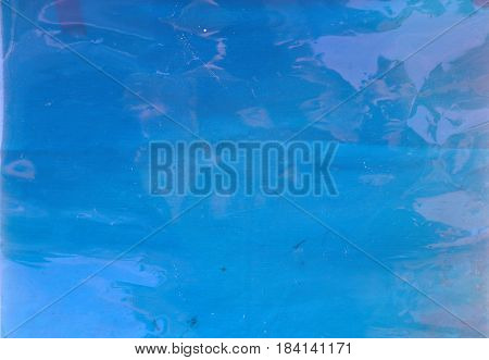 Abstract background image. Blue cellophane gel lays over a white table cloth for a unique colored and textured abstract background. Room for text or images.