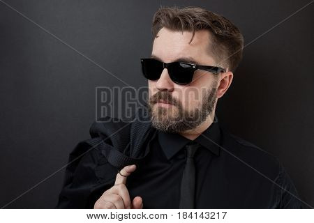 A Brutal Man With A Beard And A Stylish Hairstyle In A Black Shirt And Tie Is Holding His Jacket. Yo