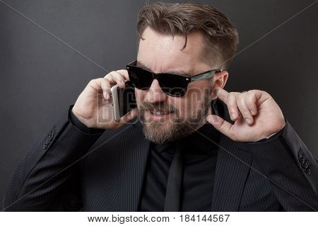 A Businessman In A Black Suit And Glasses Is Talking On The Phone. He Does Not Hear His Interlocutor