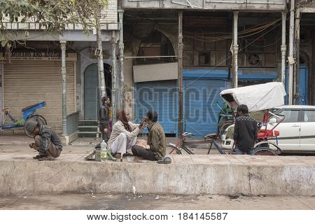 DELHI INDIA-MAR 15 : street barber at chandni chowk. this service is only in the morning. chandni chowk is famous market of Delhi on march 15 2015 india