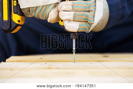 Close up of pair of hands in work gloves drilling a screw into wood with an electric drill