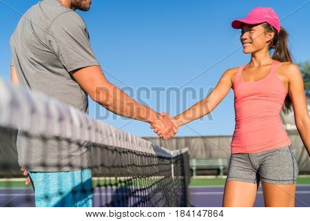 Tennis players shaking hands at court net at end of fun game. Man and woman playing together recreational tennis handshaking. Two people sports.