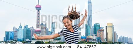 Happy Asian woman having fun dancing of joy in front of Shanghai skyline on The Bund. China travel healthy lifestyle. Happiness concept in urban city. Young adult in her 20s living active life.