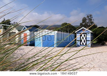 Shades of blue and white Beach huts in a row along a sandy Australian beach