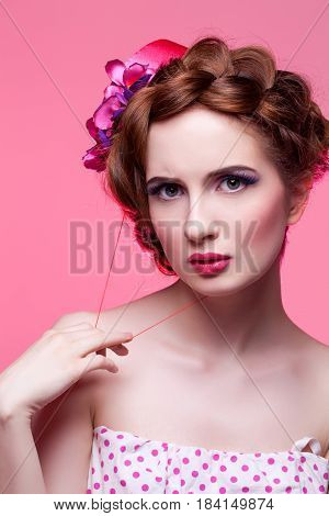 Beautiful young woman with red braided hair, bright make-up and small fancy hat over pink background. Pin up style. Copy space.