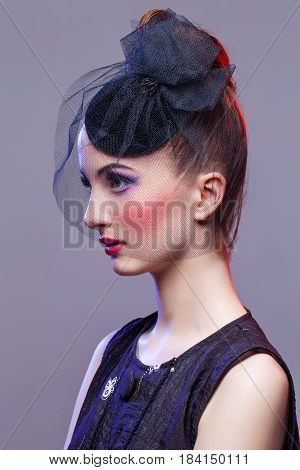 Beautiful young woman in small black veil hat cap with hairdo and bright purple tone make-up. Doll style. Beauty shot on grey background. Copy space.