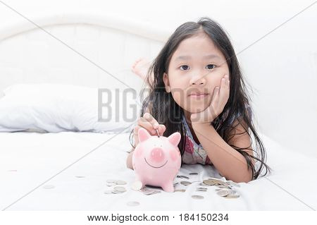 Cute Asian Girl Putting Coin To Piggy Bank On Bed.