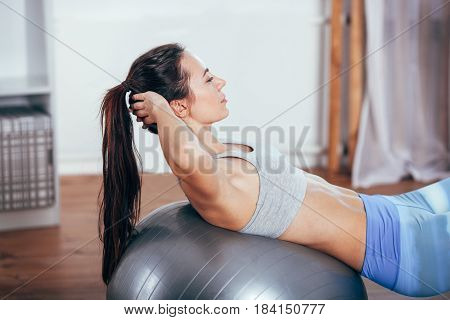 Young brunette sportswoman doing exercises with ball on a mat at home