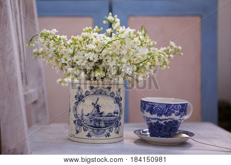 Still life with white flowers in the porcelain vase and porcelain cup in the morning light