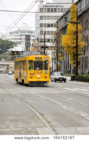 Kumamoto Japan -December 15 2009: Classic yellow tram of Kumamoto city with yellow ginko leaves background