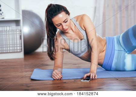 Slim fitness young brunette woman Athlete girl doing exercise at home and using smarthpone