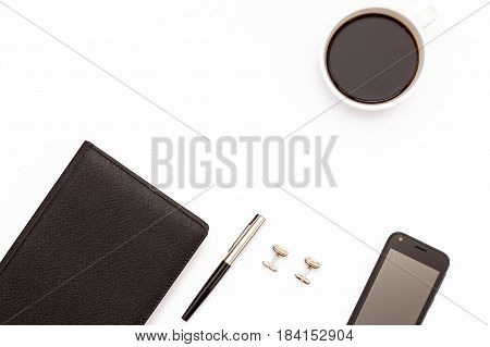 Black Diary, Cufflinks, Pen, Smartphone And Cup Of Black Coffee On A White Background. Minimal Conce
