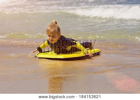 Little baby girl - young surfer with bodyboard has fun on sea beach. Family lifestyle, people outdoor water sport lessons and swimming activity on summer vacation with child in adventure surf camp.