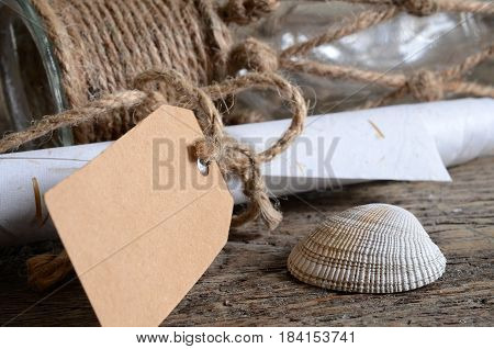 A close up image of various small seashells and rolled up note paper on a wooden table.