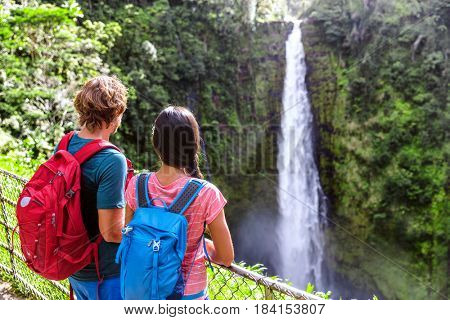 Hawaii Akaka Falls tourists at hawaiian waterfall. Young couple backpackers watching water fall on Hawaii, Big Island, USA. Travel tourism people concept.