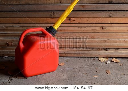 An image of a single red gas can in a garage.