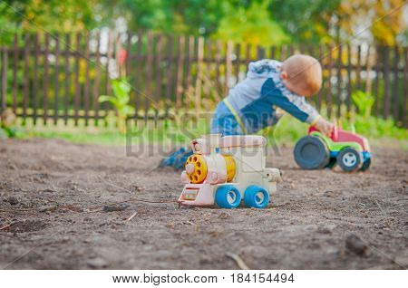 a little boy playing in the toy car in the children's village