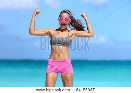 Strong fitness woman showing off muscular arms flexing biceps for fun on beach. Fit girl weight loss success. Power concept. poster