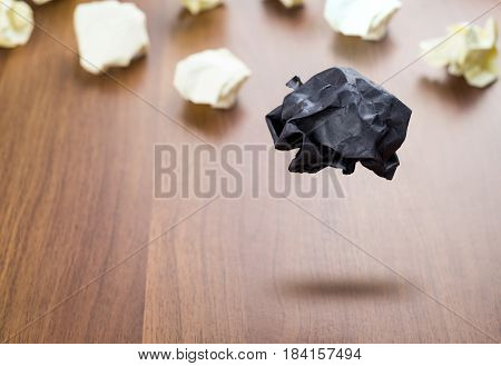 Black Crumpled Paper Ball Floating Around White Paper Ball On Wood Table, Business Concept