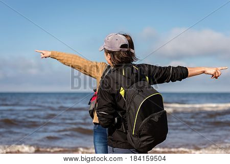 JURMALA, LATVIA - AUGUST 24 2014: Two unknown girls with hands showing different directions.