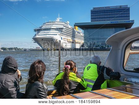 Amsterdam Netherlands - September 9 2015: Tourists in a tourboat viewing the cruise ship Costa Pacifica moored at the quay of the river IJ in Amsterdam Netherlands