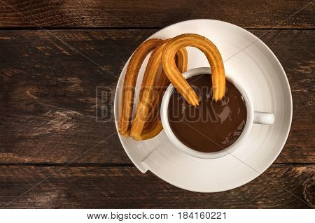 An overhead photo of churros, traditional Spanish, especially Madrid, dessert, particularly for Sunday breakfast, with a cup of hot chocolate and a place for text