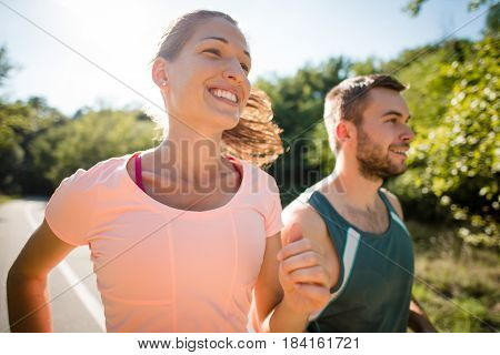 Closeup of smiling couple jogging together in summer sunny nature