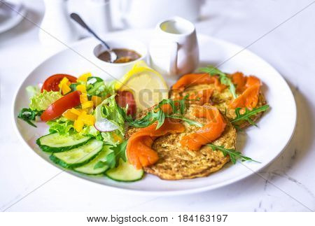 Potato pancakes with sauce. Vegetable fritters. Latkes on white plate, served with salt salmon.