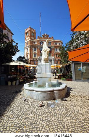 CADIZ, SPAIN - SEPTEMBER 8, 2008 - Marble fountain in the Plaza de las Flores with flower stalls cafes and the Post Office building to the rear Cadiz Cadiz Province Andalusia Spain Western Europe, September 8, 2008.