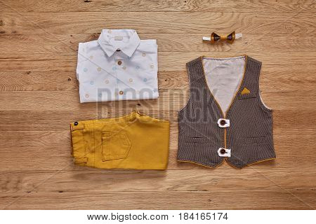 Top view of the kids fashion clothes with accessories on the wooden background. White shirt with print, brown vest, bowtie and brown pants. Elegant clothes for little boys. Concept of the children's fashion. Spring or summer clothes.