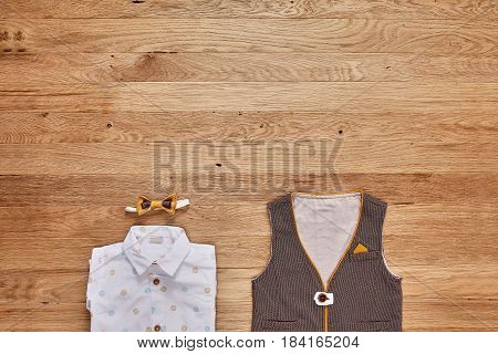 Top view of the kids fashion clothes with accessories on the wooden background. White shirt with print, brown vest and bowtie. Elegant clothes for little boys. Concept of the children's fashion. Spring or summer clothes.