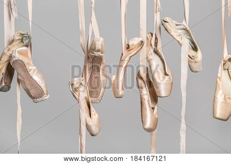 Several hanging beige ballet shoes on the gray background in the studio. Closeup. Horizontal.