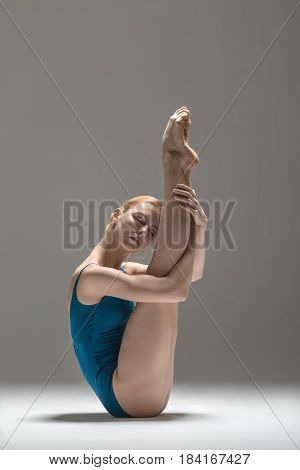 Delightful ballerina with closed eyes presses her barefoot legs to her head and torso while sits on the floor on the gray background in the studio. She wears a blue leotard. Vertical.