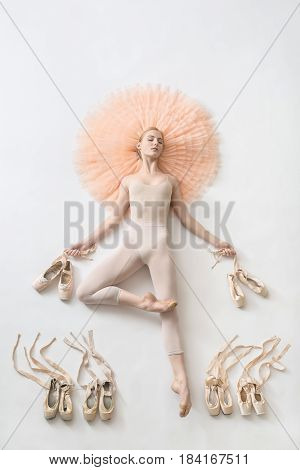 Amazing ballerina with closed eyes lies in passe on the peach tutu on the floor and holds pointe shoes in the studio. She wears a light dance wear. On the sides of her legs there are ballet shoes.