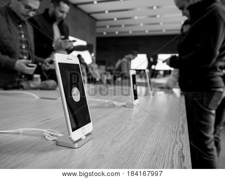 STRASBOURG; FRANCE - APR 27; 2016: Black and white image of latest iPhone 7 and iPhone 7 Plus in Apple Store with screensaver dedicated to Earth Day; - customers shopping testing in the background
