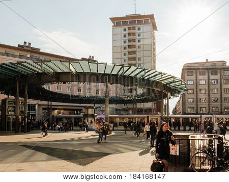 STRASBOURG FRANCE - APR 27 2017: Busy center of the French city of Strasbourg Alsace with tramways and commuters pedestrians walking under architectural station l'Homme de Fer on a sunny evening