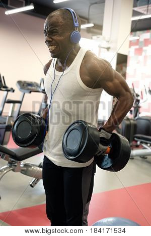 Muscular Black Man Doing Exercises With Dumbbells At Gym