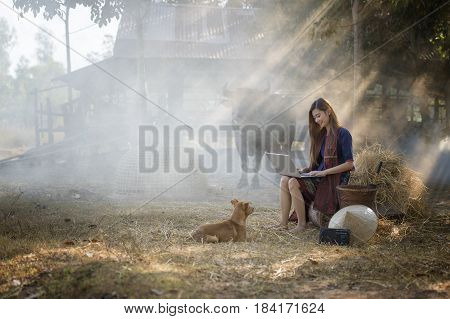 Young pretty business woman with notebook at outdoor and dog looking to her on buffalo and farm background