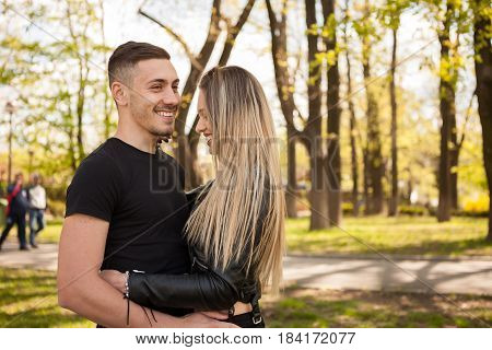 Couple posing at camera in the park. In love and relationship. Happines and love