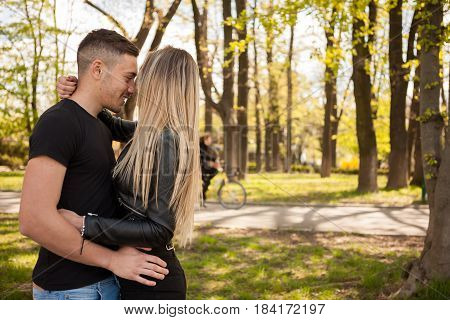 Beautiful young couple taking a walk in the park. In love and relationship. Happines and love
