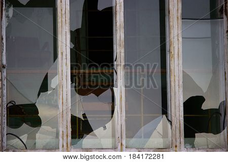 Broken windows in an old abandoned brick building