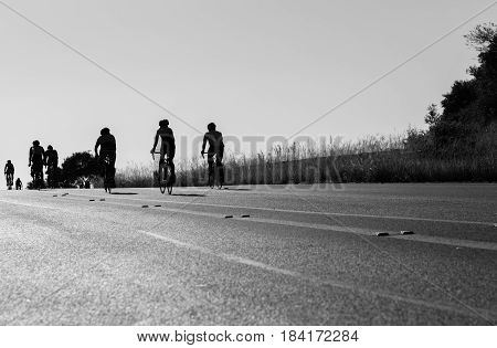 Cyclists Cycling up hill silhouetted road race