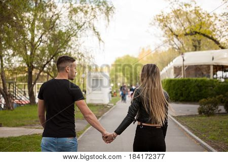 Beautiful young couple holding hands in the park. In love and relationship. Happines and love