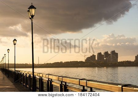 seafront with fence and street lanterns. clouds